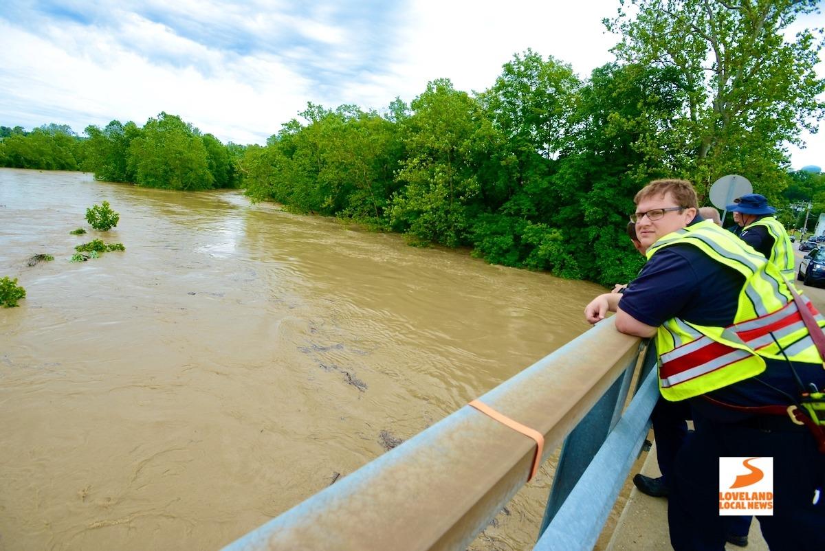 Firefighter on bridge watching river for kayak