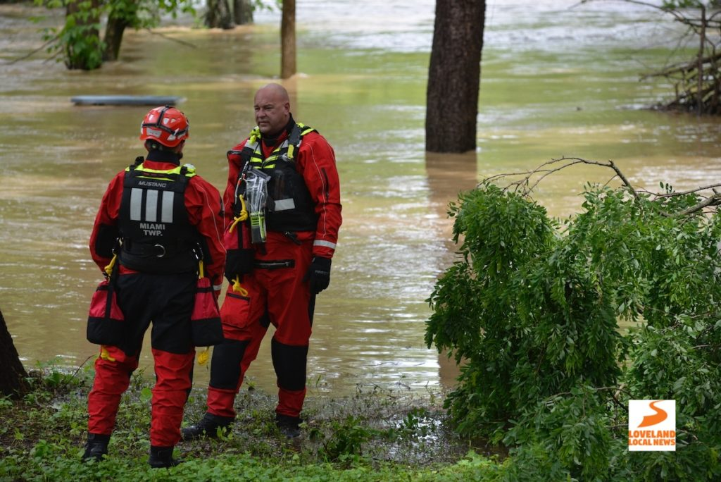 Firefighters in dive gear stand near the flooded river
